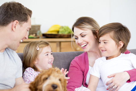 cosy: Close up shot of a happy family sitting together on the sofa in the living room of their home. They have the dog with them and are talking and smiling.