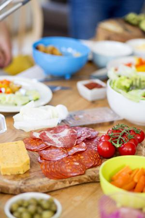 jamones: comida de estilo mediterráneo en una tabla que incluye jamones curados, quesos, tomates y ensalada. Foto de archivo