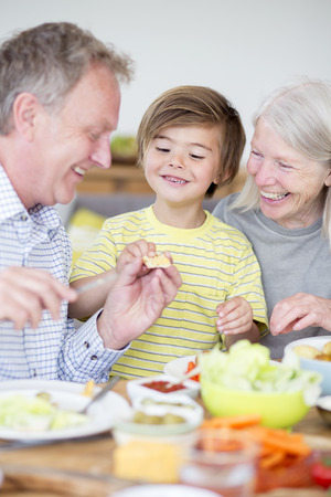 only senior adults: Little boy is sitting at the dining table with his grandparents in their home. His grandfather is buttering some bread and giving it to his grandson. Stock Photo