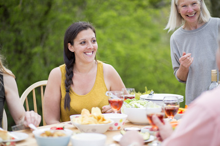 Woman enjoying herself at a family garden party. They are eating mediterranean style food.
