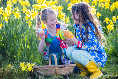Two little girls are in a daffodil field looking for easter eggs together during an easter egg hunt. They have a basket with them and are holding some of the eggs with pride. Imagens - 70256557