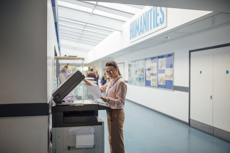 school work: Teacher is printing off work sheets for her next lesson using the printer in the school hall. Stock Photo
