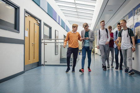 Group of teenage boys are walking down the school hall together to go for their lunch break. They are talking and laughing and some of the boys are using smart phones. Stock Photo