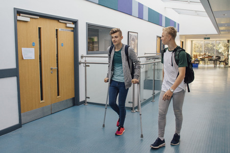 Teen students are walking down the school hall together. They have left lesson early, as one of the boys is on crutches and requires assistance from his friend.