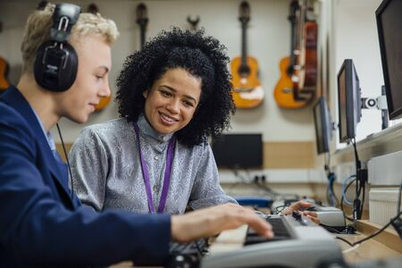 one female: Female teacher is sitting with one of her students in a music lesson at school. He is learning to play the keyboard and is wearing headphones.  Stock Photo