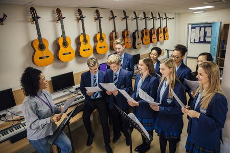 Klasse van tieners zijn in hun muziekles op school. Er is een vrouwelijke leerkracht en de klas oefenen koor met haar.