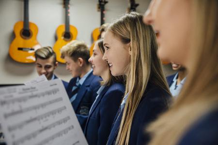 Ciérrese encima de tiro de los estudiantes del coro que cantan en su lección de música en la escuela.