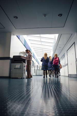 Group of students are walking down the corridor of their school. There is a female teacher using the printer. Stockfoto