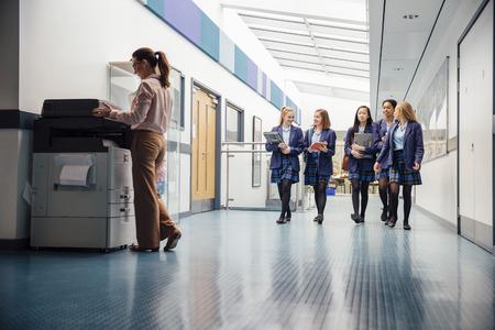 Groep tienermeisjes lopen door de schoolzaal met boeken en laptops in hun armen. Ze praten en lachen terwijl ze lopen en er is een vrouwelijke leraar die de printer gebruikt. Stockfoto
