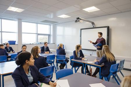 Mannelijke leraar leert een groep tieners in een middelbare schoolles.