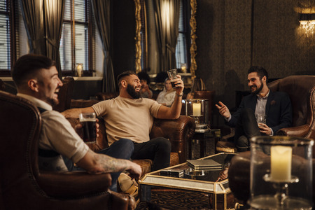 Three men are enjoying drinks in a bar lounge. They are talking and laughing while drinking pints of beer.