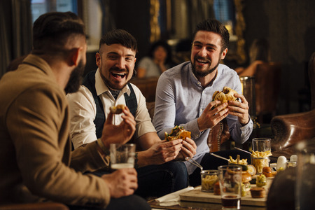 Three men are sitting together in a bar/restaurant lounge. They are laughing and talking while enjoying burgers and beer.