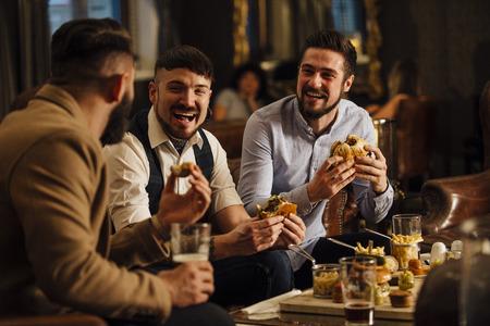 3 人の男性は、バーレストラン ラウンジで一緒に座っています。彼らは笑って、ハンバーガーとビールを楽しみながら話しています。
