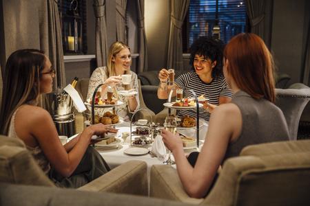 4 명의 여자들이 함께 앉아 오후의 차를 즐기고 있습니다. 그들은 말하고 먹고 샴페인과 차를 마시고 있습니다.