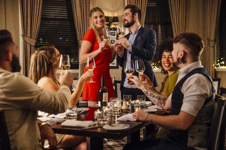 restaurant dining: Friends are at a formal meal together. A couple are standing together at one end of the table, making a toast to which everyone is raising their glass. Stock Photo