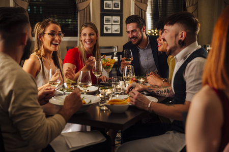 Group of friends are enjoying a meal together. They are talking and laughing while eating their starters and drinking champagne.