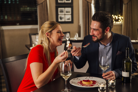 Couple are sharing a dessert in a restaurant on Valentines Day in a restaurant. Stock Photo
