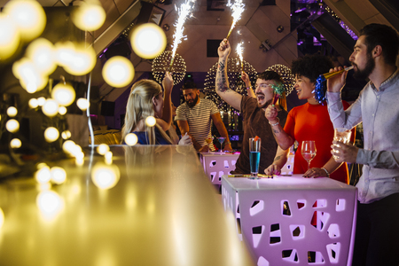 Group of friends are partying in a nightclub with indoor sparklers and alcoholic drinks.