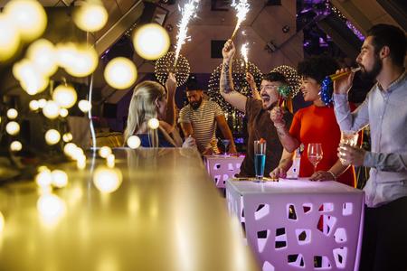 bebidas alcohÓlicas: Grupo de amigos están de fiesta en un club nocturno con sparklers de interior y bebidas alcohólicas. Foto de archivo