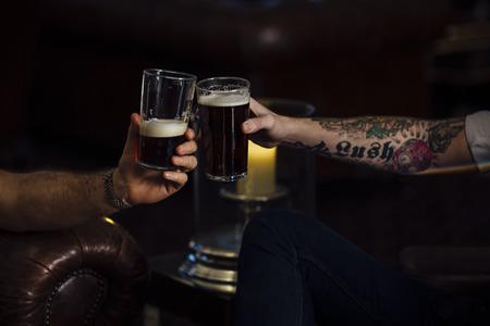 2 人の男性が彼らのパイントを乾杯のショットを閉じる。