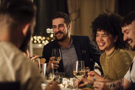 Groupe d'amis dégustant un repas dans un restaurant. Ils parlent et rient en mangeant et en buvant du vin. Banque d'images