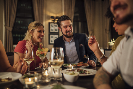 Mid adult couple are socialising over a meal in a restaurant. They are eating starters and drinking champagne while laughing and talking.  Stock Photo