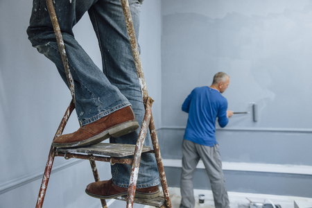 only man: Two male builders are painting a room. One man is using a ladder and only his legs are visible. The other man is in the background.