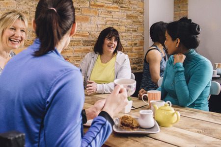 Women are sitting at a table in a cafe, socialising over tea and cake.