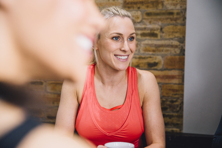 Close up shot of a woman in a cafe enjoying a cup of tea. She is socialising with her friends.