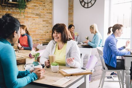 Women are sitting at a table in a cafe, socialising over coffee and tea. Stock fotó