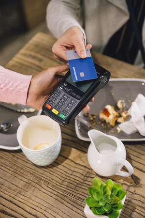 High angle view of a woman making a contactless card payment for her coffee and scone in a cafe.  Stock Photo