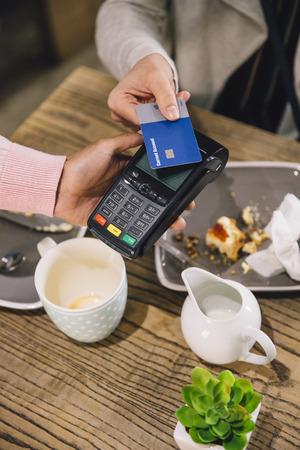 Hoge hoek oog van een vrouw die een contactloze kaart betaling voor haar koffie en scone in een cafe. Stockfoto