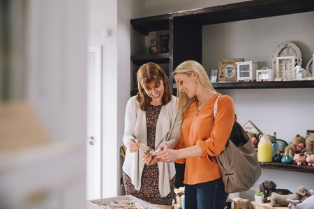 self indulgence: Two women are looking at products in a small shop together. Stock Photo
