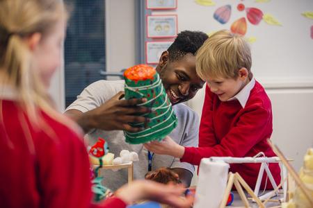 De jonge leraar helpt één van zijn primaire schoolstudenten tijdens kunst en handvaardigheidsles.