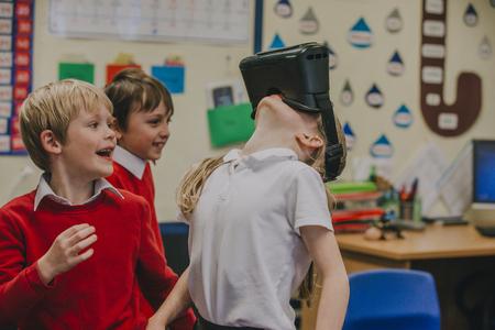 Basisschoolleerlingen experimenteren met virtual reality-headsets tijdens hun lesuren. Een jong meisje draagt de headset en laat haar hoofd achterover kantelen alsof ze naar iets boven haar kijkt.