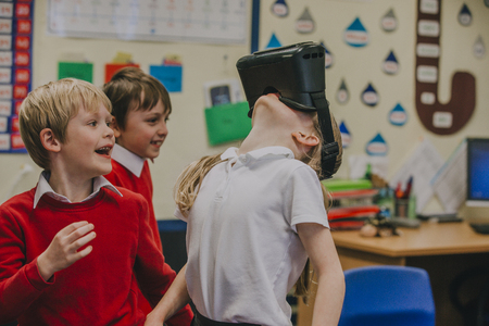 Primary school students are experimenting with virtual reality headsets in their lesson time. A young girl is wearing the headset and has her head tilted back as if she is looking at something above her. Foto de archivo