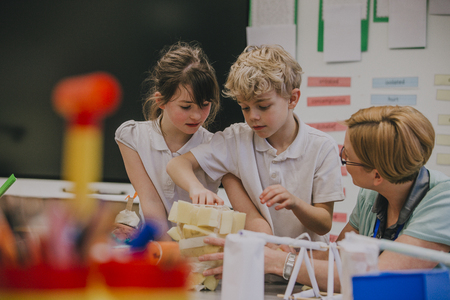 Primary school students are working on an arts and crafts project with their teacher. They are taping sponges together into a shape. Фото со стока - 77181026
