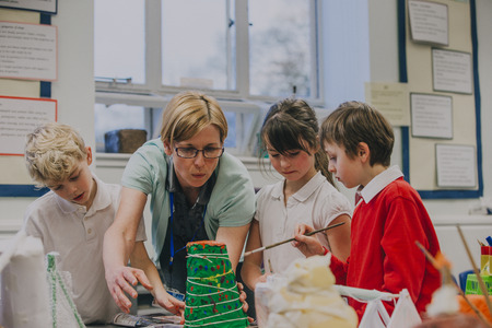 Primary school students are working with their teacher on a science project in the classroom. They are making a paper mache volcano. Stock Photo
