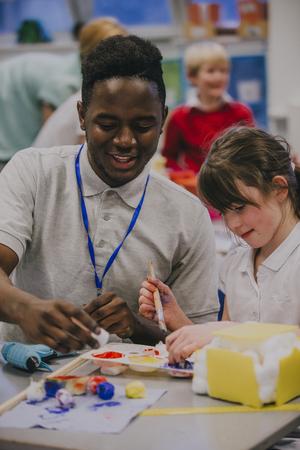 Joven maestro está trabajando con uno de sus alumnos de la escuela primaria durante una lección de arte y manualidades. Están pintando y discutiendo el proyecto. Foto de archivo - 77181029