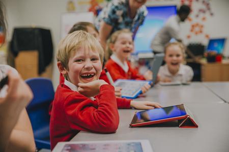 행복 한 어린 소년 학교에서 자신의 기술 수업에서 디지털 태블릿을 사용하는 동안 카메라에 웃 고있다.