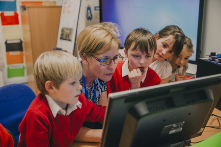 Primary school students are standing round their teacher at the computer in the classroom. They are all concentrating on something on the screen.