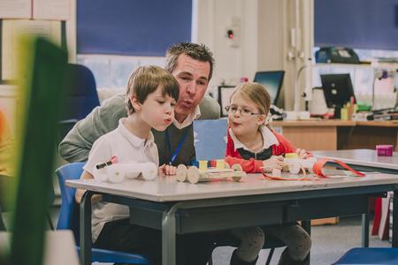 교사는 초등 학생 2 명과 함께 교실에 앉아 물리 프로젝트를 테스트 할 수 있도록 돕고 있습니다. 그들은 장난감을 움직이기 위해 입을 불고 공기를 만 스톡 콘텐츠