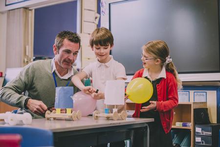 Grundschullehrer hilft zwei seiner Schüler mit einem MINT-Projekt. Sie bauen etwas mit recycelten Gegenständen und Handwerksausrüstung. Standard-Bild - 77482451