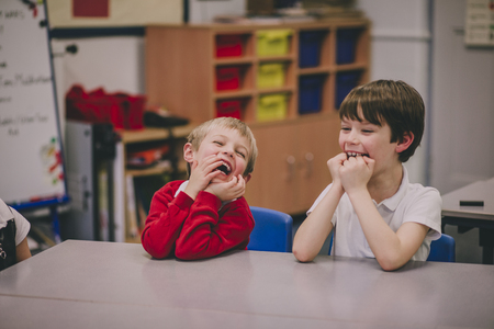 Two little boys are at school, sitting at a table in their classroom. They are both hysterically laughing at something.