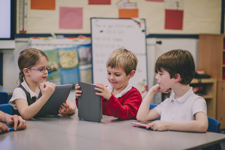 Table of primary school students in a classroom are using digital tablets to work on. Stock Photo