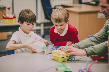 De leraar helpt zijn basisschoolstudenten in de klas met hun STEM-project. Stockfoto