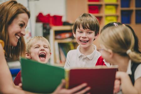 Nauczycielka siedzi w klasie ze swoimi uczniami ze szkoły podstawowej, czytając im bajkę.