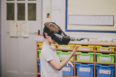 Little boy is experimenting with virtual reality in the classroom at school. Stock Photo