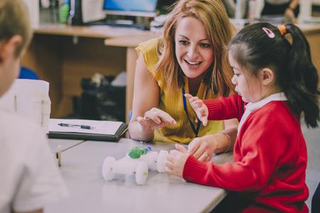 先生は彼女の小学生で彼女の教室でテーブルに座っています。彼らはリサイクルのオブジェクトや工芸品の機器から車を造った、それ動作すること