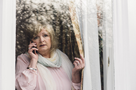 lady on phone: Senior woman is reporting a neighborhood crime to the police on the phone. She is looking out her window.